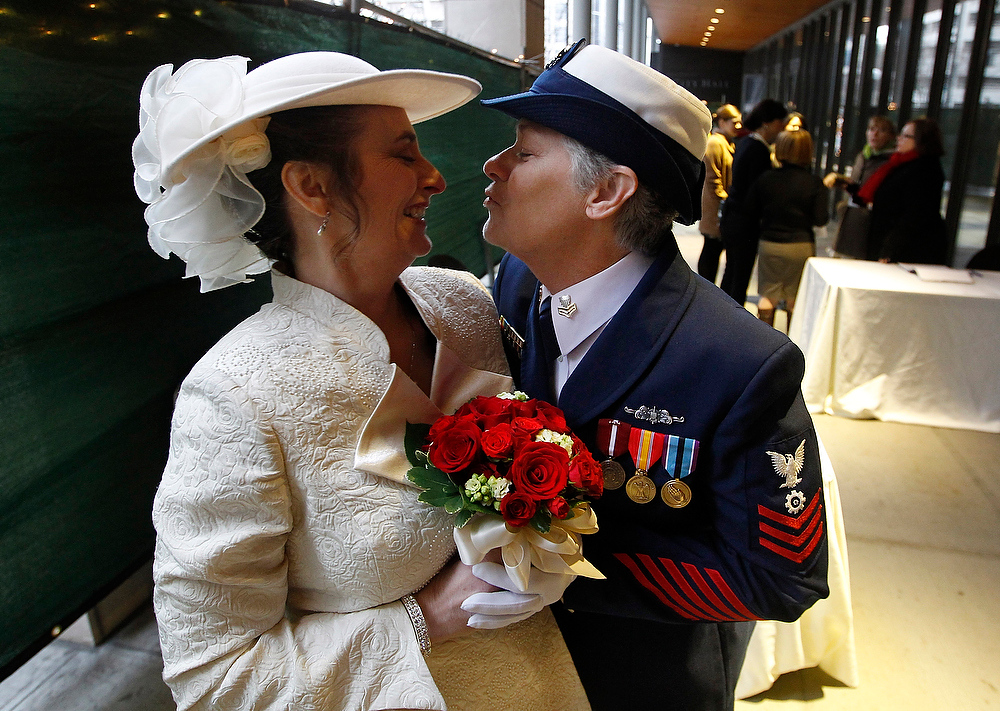 . Retired U.S. Coast Guard Petty Officer 1st Class Nancy Monahan, right, wears her dress uniform as she leans in to kiss her soon-to-be bride Deb Needham while they wait at Seattle City Hall to become among the first gay couples to legally wed in the state, Sunday, Dec. 9, 2012, in Seattle. The couple is from Renton, Wash. Gov. (AP Photo/Elaine Thompson)