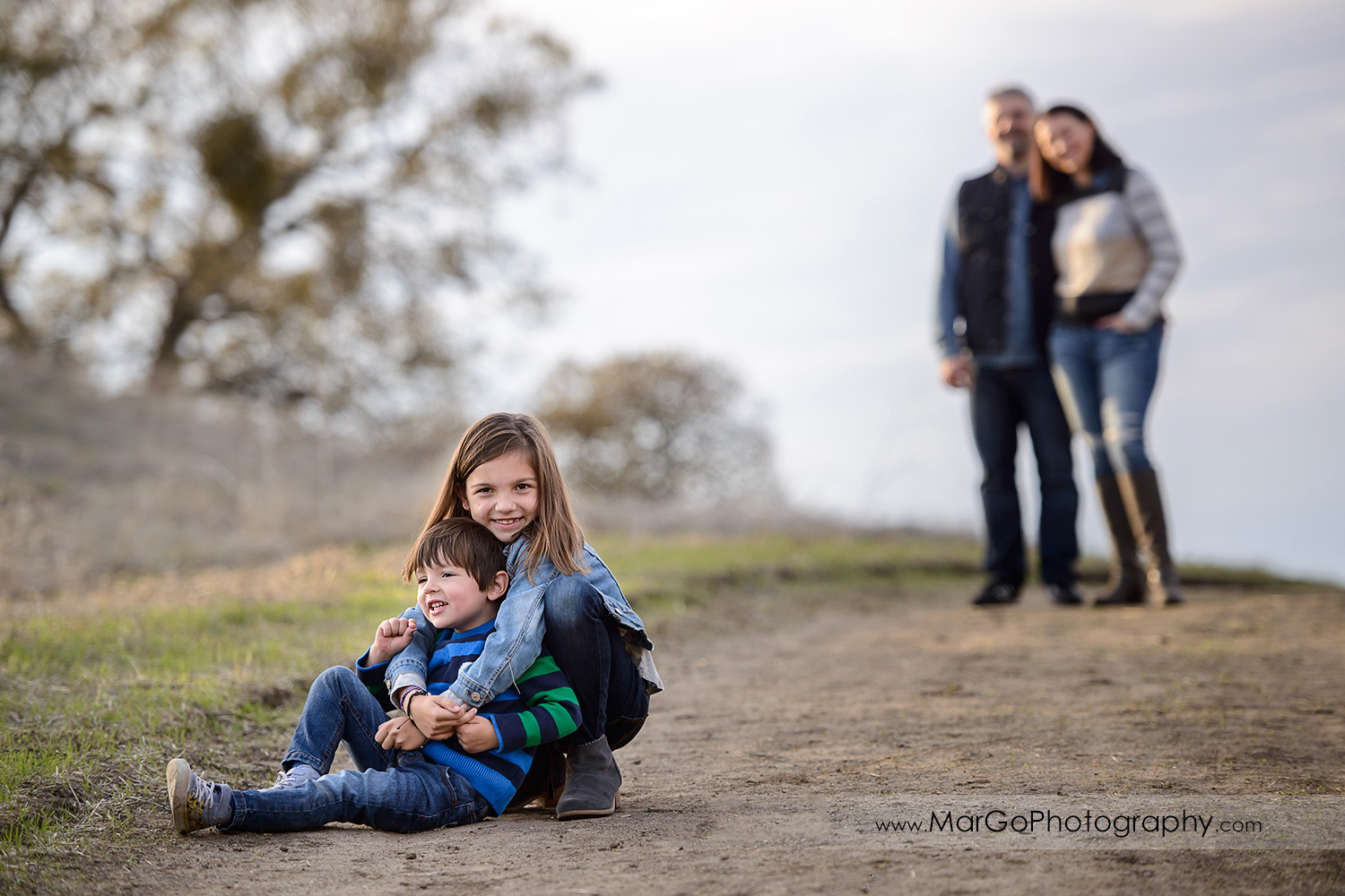young girl hugging little boy with mother and father standing in background during family session at Diablo Foothills Regional Park in Walnut Creek