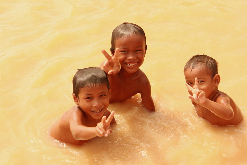 Some kids swimming in a pond behind one of the patient's house