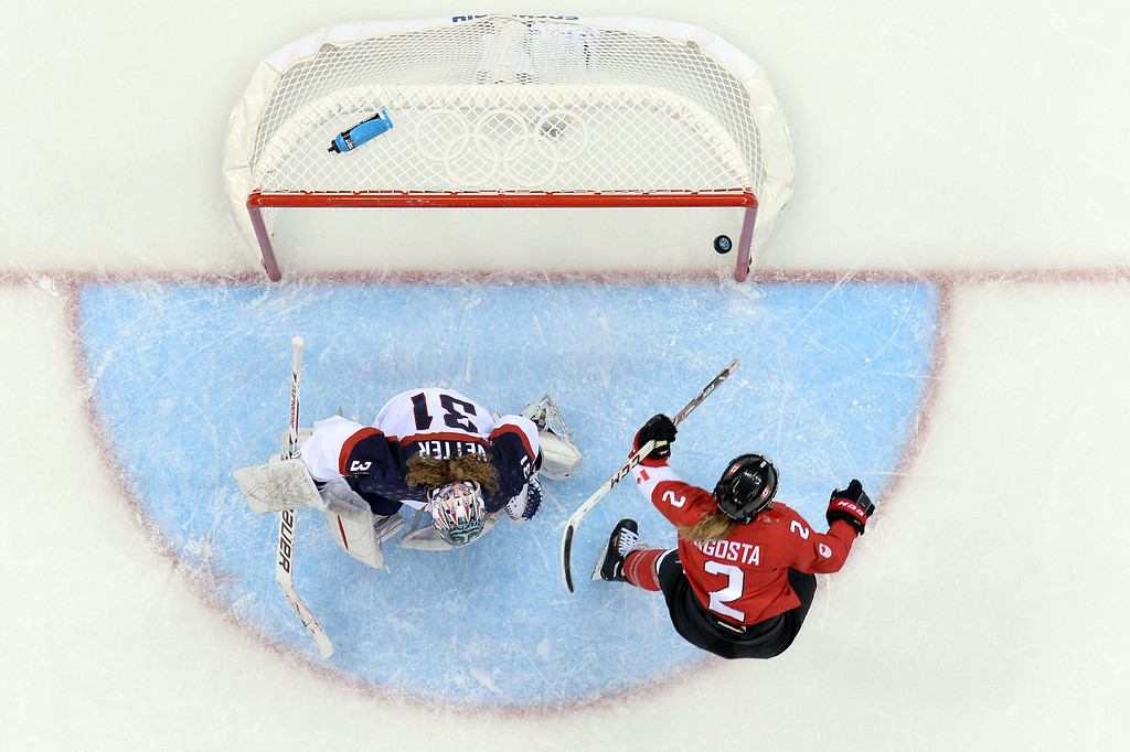 . Canada\'s Meghan Agosta-Marciano (bottom) scores her team\'s third goal against US goalkeeper Jessie Vetter during the Women\'s Ice Hockey Group A match between Canada and USA at the Sochi Winter Olympics on February 12, 2014 at the Shayba Arena. AFP PHOTO / JONATHAN NACKSTRAND/AFP/Getty Images
