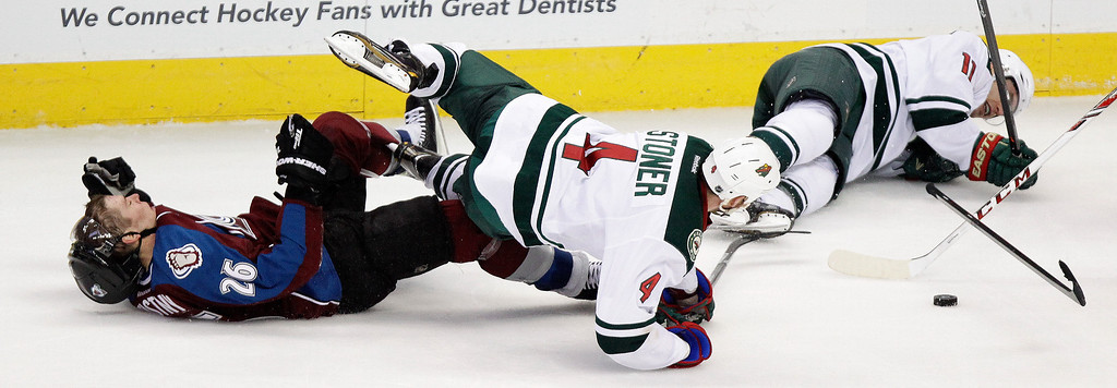 . Colorado Avalanche\'s Paul Stastny (26) collides with Minnesota Wild\'s Clayton Stoner (4) and Zach Parise (11) during the third period of an NHL hockey game on Thursday, Jan. 30, 2014 in Denver. The Avalanche won 5-4. (AP Photo/Barry Gutierrez)
