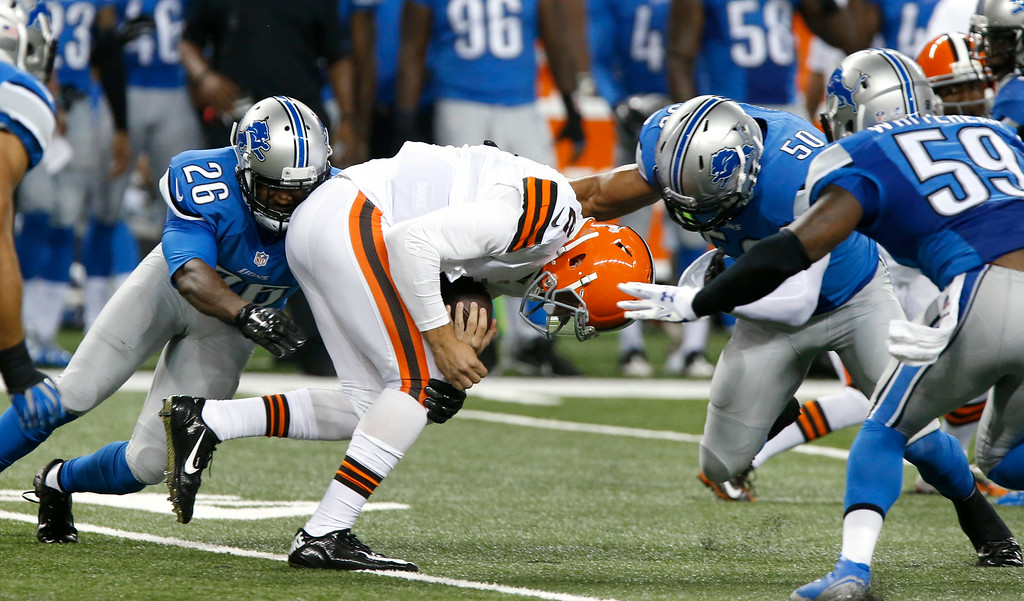 . Cleveland Browns quarterback Johnny Manziel (2) is brought down by Detroit Lions strong safety Don Carey (26), Detroit Lions linebacker Travis Lewis (50) and Detroit Lions linebacker Tahir Whitehead (59) in the first half of a preseason NFL football game at Ford Field in Detroit, Saturday, Aug. 9, 2014.  (AP Photo/Duane Burleson)