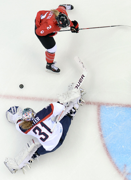 . Canada\'s Meghan Agosta-Marciano (top) vies for the puck with US goalkeeper Jessie Vetter during the Women\'s Ice Hockey Group A match between Canada and USA at the Sochi Winter Olympics on February 12, 2014 at the Shayba Arena. AFP PHOTO / JONATHAN NACKSTRAND/AFP/Getty Images