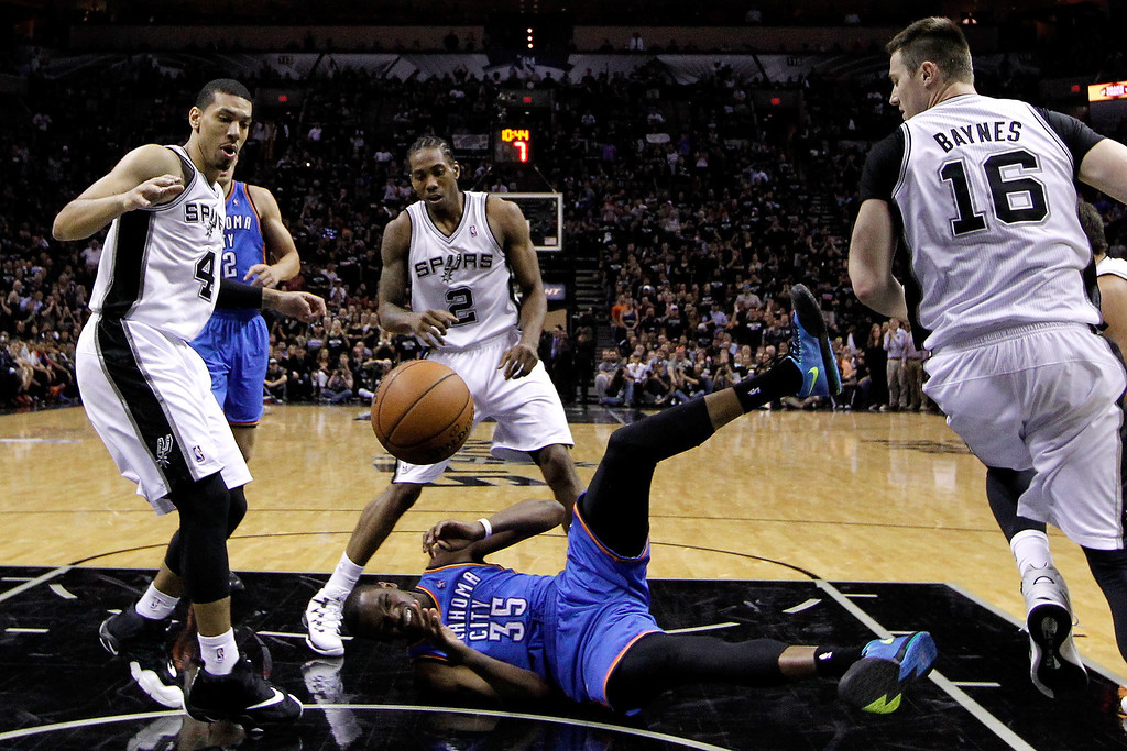 . Kevin Durant #35 of the Oklahoma City Thunder on the floor as the ball flies over his head against Danny Green #4 and Kawhi Leonard #2 of the San Antonio Spurs in the second half in Game One of the Western Conference Finals during the 2014 NBA Playoffs at AT&T Center on May 19, 2014 in San Antonio, Texas.  (Photo by Chris Covatta/Getty Images)
