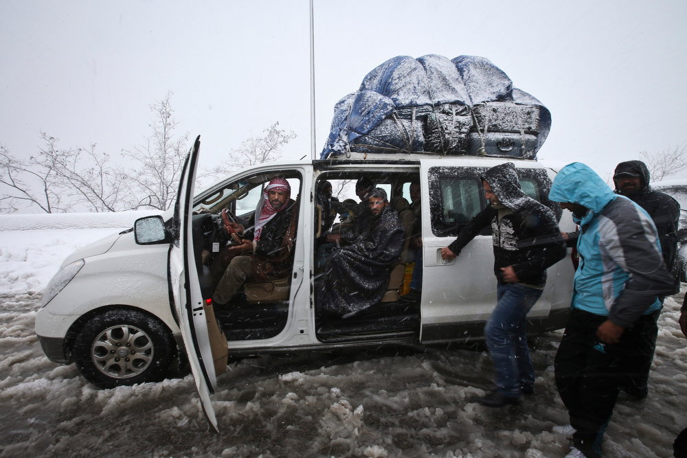 Description of . Syrian citizens make their way to Beirut on the Beirut-Damascus highway, in Sawfar mountain, Lebanon, Tuesday Jan. 8, 2013. Lebanon has been hit with a snow storm that has blocked roads in the mountains and brought heavy rain showers to the capital Beirut and other coastal areas since Sunday and according to the Lebanese meteorology, the storm will continue until late Thursday. (AP Photo/Hussein Malla)