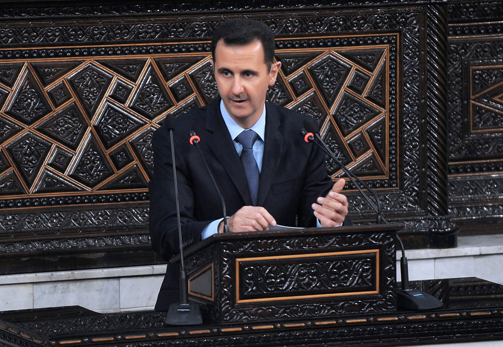""". In this photo released by the Syrian official news agency SANA, Syrian President Bashar Assad addresses the nation during a speech at the Parliament in Damascus, Syria, Wednesday, March 30, 2011. Syria\'s president has blamed the wave of protests against his authoritarian rule on \""""conspirators\"""" _ but he failed to offer any concessions to appease the extraordinary wave of dissent. (AP Photo/SANA)"""