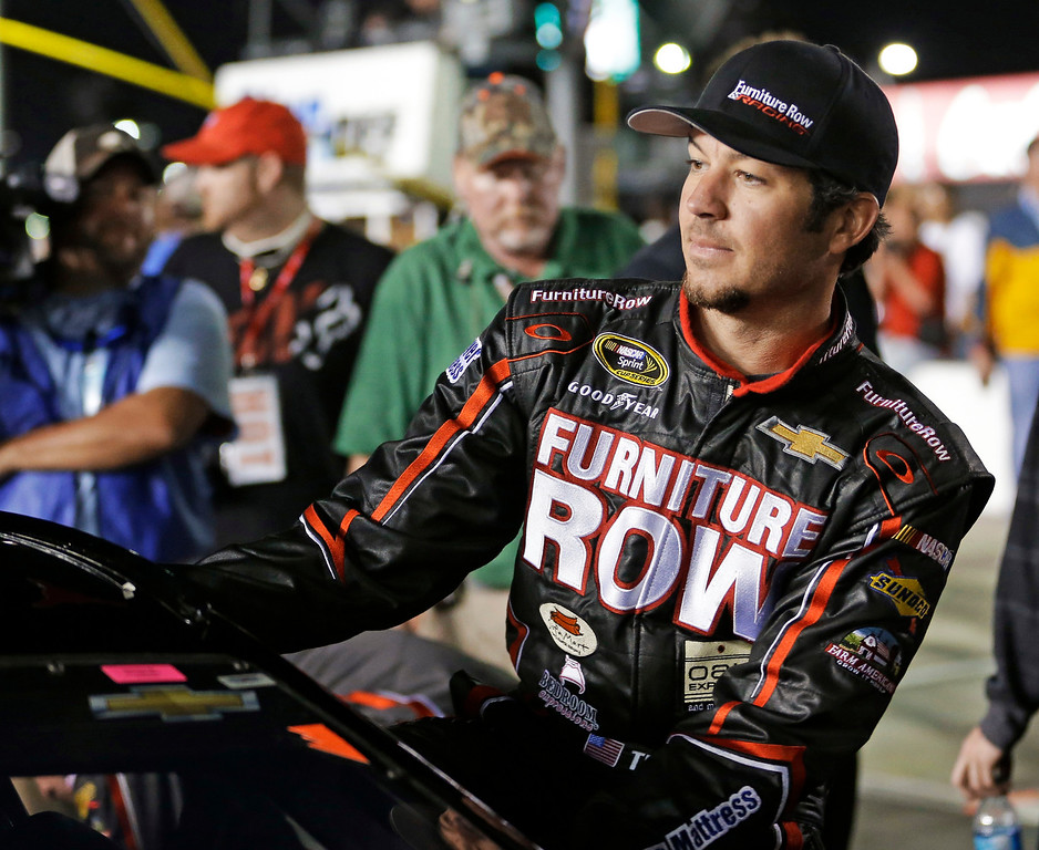 . Martin Truex Jr climbs into his car before the second of two NASCAR Sprint Cup series qualifying auto races at Daytona International Speedway in Daytona Beach, Fla., Thursday, Feb. 20, 2014. (AP Photo/John Raoux)