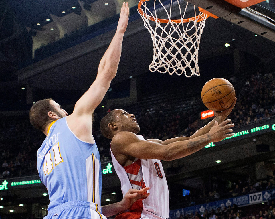 . Toronto Raptors\' DeMar DeRozan drives to the net despite pressure from Denver Nuggets\' Kosta Koufos during the first half of an NBA basketball game in Toronto on Tuesday, Feb. 12, 2013. (AP Photo/The Canadian Press, Chris Young)