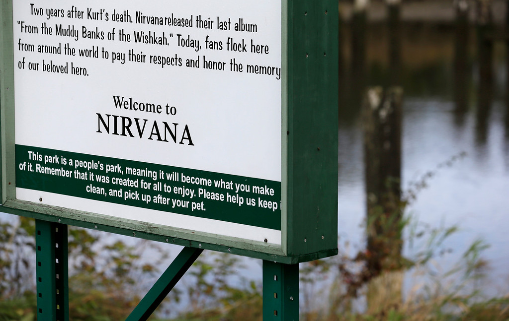 """. This photo taken Monday, Sept. 23, 2013, show\'s a sign for \""""Kurt Cobain Landing,\"""" a tiny park blocks from the childhood home of the late frontman of Nirvana, overlooking the Wishkah River in Aberdeen, Wash. (AP Photo/Elaine Thompson)"""