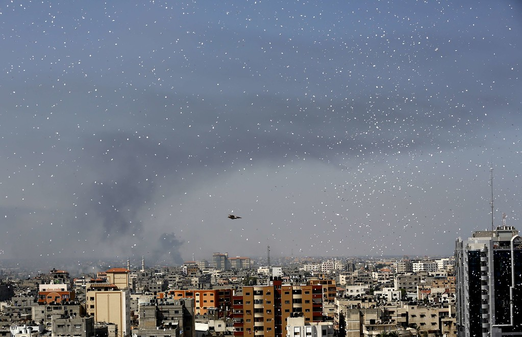 ". Flyers are dropped over Gaza City by the Israeli army urging residents to evacuate their homes on July 30, 2014. Israeli bombardments early on July 30 killed ""dozens\"" of Palestinians in Gaza, including at least 16 at a UN school, medics said, on day 23 of the Israel-Hamas conflict. AFP PHOTO / MOHAMMED  ABED/AFP/Getty Images"