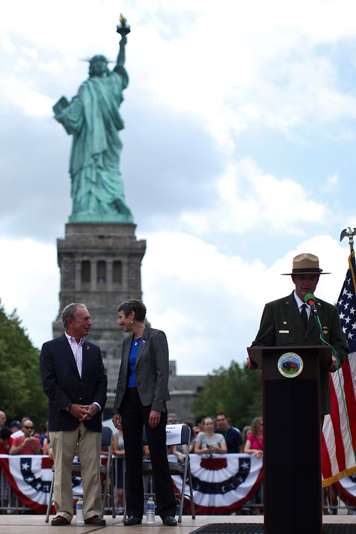 . Secretary of the Interior Sally Jewell (C) speaks with New York City Mayor Michael Bloomberg (L) while they attend a ceremony to reopen the Statue of Liberty and Liberty Island to the public in New York July 4, 2013. Under steamy summer skies, tourists in New York flocked to ferries headed for the Statue of Liberty, re-opening with an Independence Day ceremony after closing in October as Superstorm Sandy approached. REUTERS/Eduardo Munoz