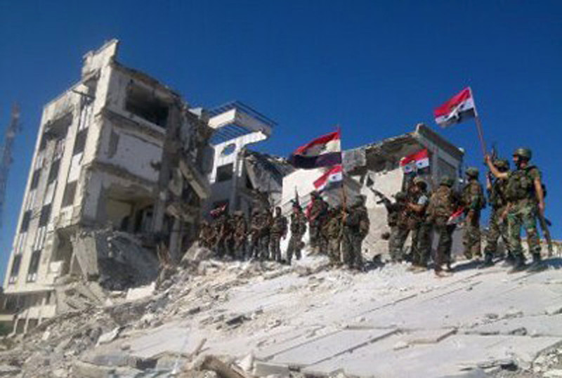 . In this Wednesday, June 5, 2013 file photo released by the Syrian official news agency SANA, Syrian army troops hold up national flags in the town of Qusair, near the Lebanon border, Homs province, Syria. Two years ago, it seemed almost inevitable that President Bashar Assad would be toppled. Almost no one thinks that now. As he prepares for elections through which he is set to claim another seven-year mandate for himself, the momentum in the civil war is clearly in Assad\'s favor. (AP Photo/SANA, File)