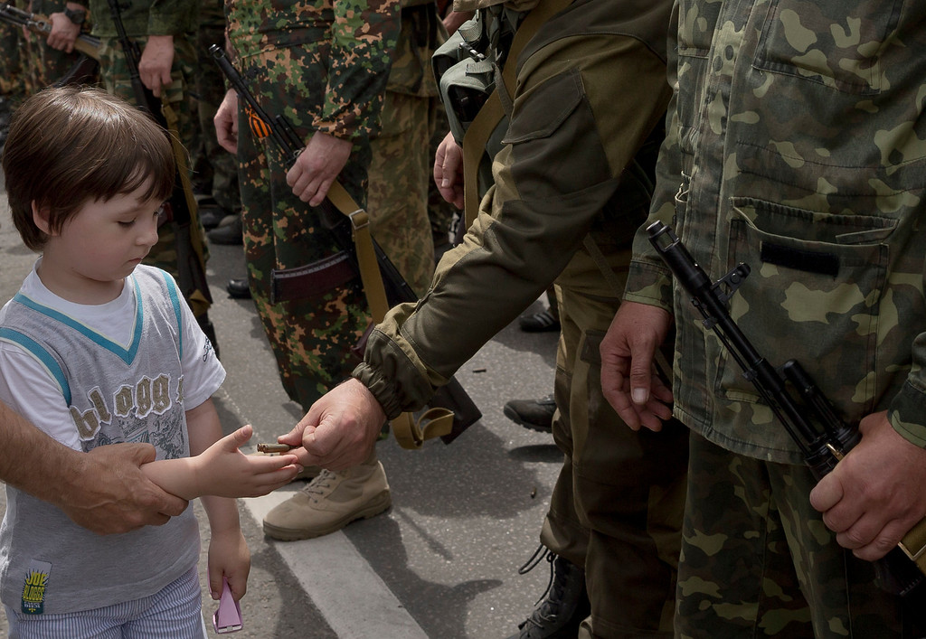 """. A man holds a child\'s hand to receive empty bullet cartridges offered by a pro-Russian gunman in Lenin square in Donetsk, Ukraine, Sunday, May 25, 2014. A convoy of an armored personnel carrier and seven trucks carrying several hundred heavily armed men drove through central Donetsk early Sunday afternoon and gunmen got out of the trucks, stood to attention and shot into the air in jubilation as a crowd of several thousand supporters cheered them and chanted: \""""Heroes!\"""". Ukraine\'s critical presidential election got underway Sunday under the wary scrutiny of a world eager for stability in a country rocked by a deadly uprising in the east. (AP Photo/Vadim Ghirda)"""
