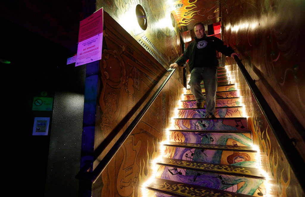 ". Jeff Call, owner of the Stonegate pizza-and-rum bar in Tacoma, Wash., walks Saturday, March 2, 2013, down the stairs that lead to the second-floor private club lounge area of the bar that allows the use of marijuana in the form of non-smoke vapor. Call charges patrons a small fee to become a member of the private second-floor club, which prohibits smoking marijuana, but does permit ""vaporizing,\"" a method that involves heating the marijuana without burning it. Last fall, Washington and Colorado became the first states to legalize marijuana use for adults over 21. (AP Photo/Ted S. Warren)"