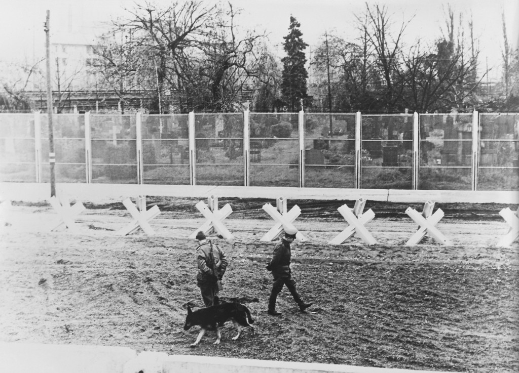 . East German border guards, seen from Wedding in West Berlin, on patrol with a guard dog in the \'death strip\' between the fences of the Berlin Wall, Germany, December 1967. (Photo by Keystone/Hulton Archive/Getty Images)