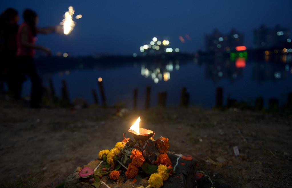 . Indian children burst fire crackers as Hindu devotees perform rituals during Chhath Puja in Kolkata on November 8, 2013.    AFP PHOTO/Dibyangshu  SARKAR/AFP/Getty Images