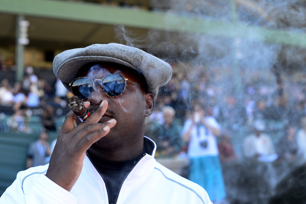 . Eric Williams, of Chicago, enjoys a cigar during the Breeders\' Cup at Santa Anita Park in Arcadia Friday, November 1, 2013. (Photo by Sarah Reingewirtz/Pasadena Star-News)