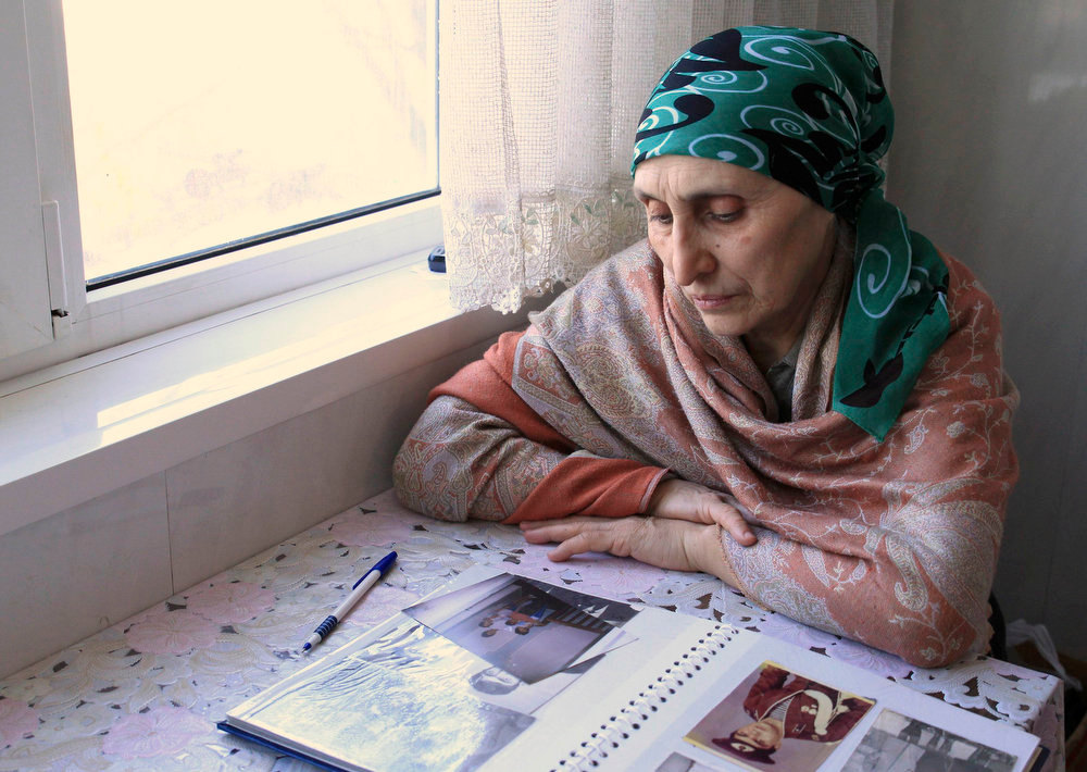 . Patimat Suleimanova, aunt of Boston bombing suspects Dzhokhar and Tamerlan Tsarnaev, looks at photos from a family album at her house in Makhachkala, in this April 22, 2013 file picture.  REUTERS/Stringer/Files