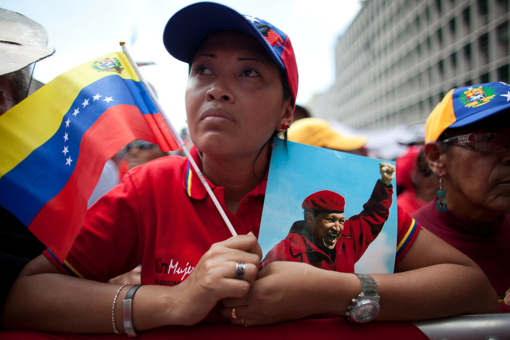 """. A woman holds a picture of Venezuela\'s President Hugo Chavez and the country\'s national flag during an event commemorating the violent street protests of 1989 known as the \""""Caracazo,\""""  in Caracas, Venezuela, Wednesday, Feb. 27, 2013. The wave of the 1989 violent protests, seen by the Chavez government as a \""""popular uprising,\"""" was in response to the economic measures imposed by then President Carlos Andres Perez.  (AP Photo/Ariana Cubillos)"""