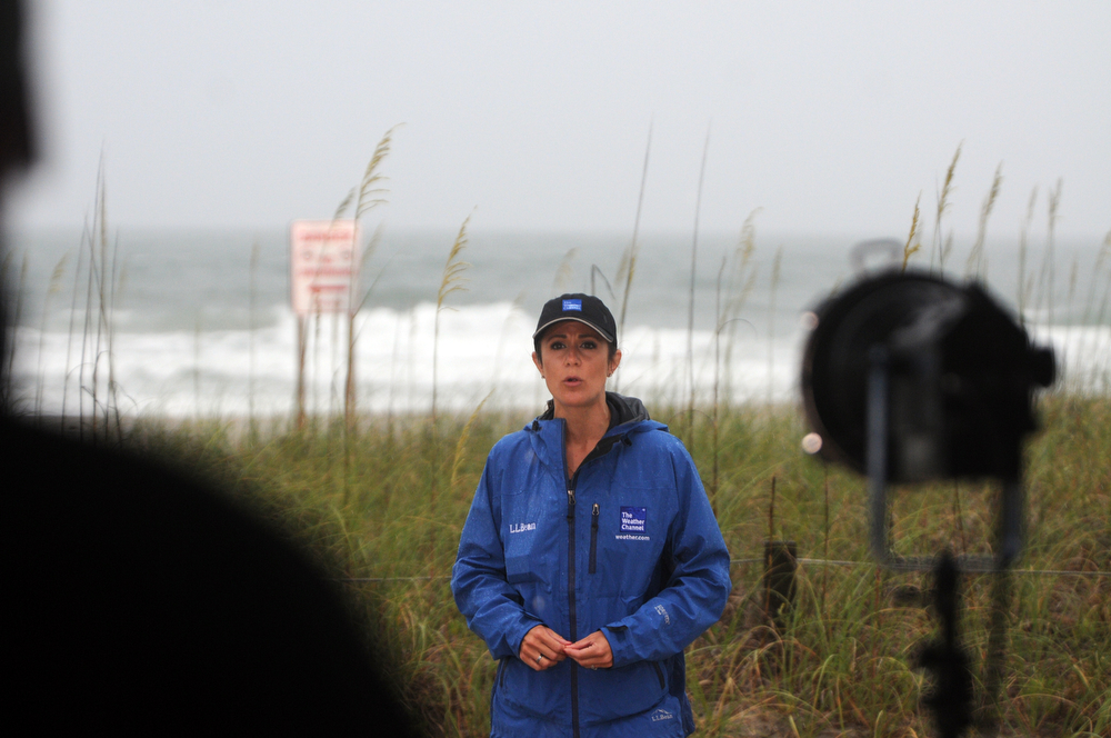 . Weather Channel correspondent Raegan Medgie reports on Hurricane Arthur near Johnnie Mercer\'s Fishing Pier at Wrightsville Beach, N.C., Thursday, July 3, 2014. Residents along the coast of North Carolina are bracing for the arrival of the Hurricane Arthur, a category one storm. (AP Photo/Wilmington Star-News, Mike Spencer)