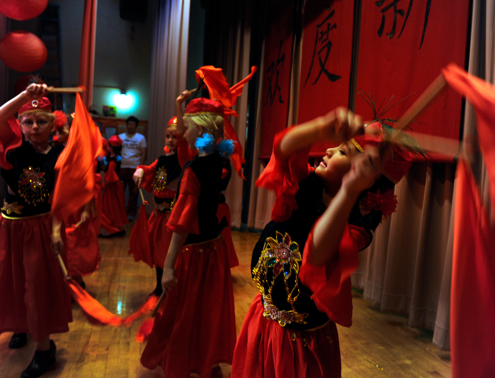 . Third-grader Avery McLaughlin, 8, right, joins her classmates in performing the Xinjiang  (Uyghur) Dance. Students at the Denver Language School ring in the Year of the Snake with their Chinese New Year celebration performance in the school auditorium. Kindergarteners through 4th grade perform traditional dances dressed in colorful Chinese costumes. According to the school principal, Chinese New Year is the most important of the traditional Chinese holidays. Families make way for  good luck by cleaning their homes symbolizing reconciliation and forgetting old grudges in exchange for peace and happiness. The Chinese New Year (Feb. 10) follows the Chinese 12 Zodiac Calendar Year designating 2013 the Year of the Snake. (Photo By Kathryn Scott Osler/The Denver Post)