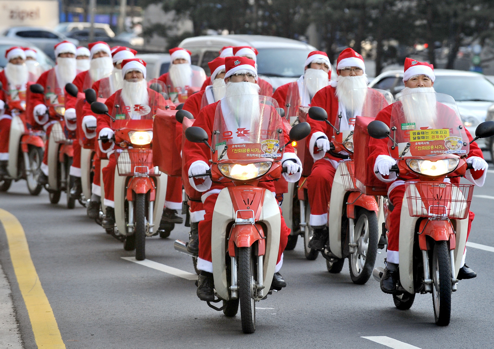 Description of . South Korean postmen wearing Santa Claus outfits ride motorbikes to deliver Christmas gifts to poor people for their charity campaign in Seoul on December 21, 2009. The donations will last for four days with 40 selected