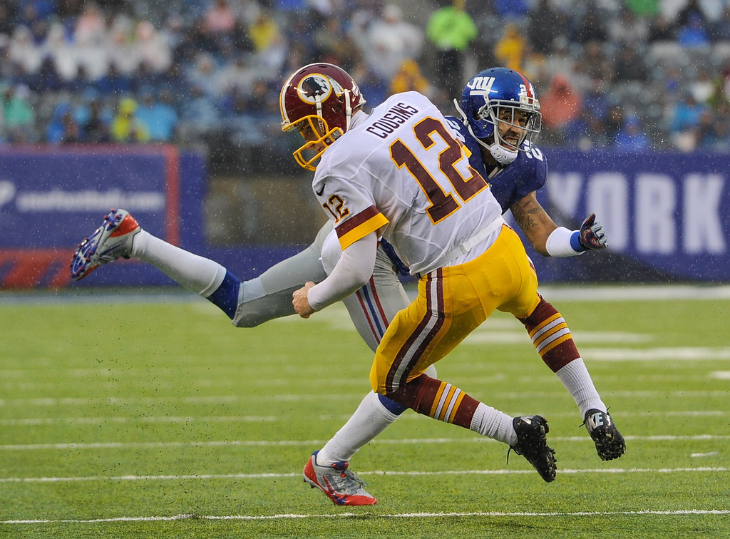 . Quarterback Kirk Cousins #12 of the Washington Redskins is hit by cornerback Terrell Thomas #24 of the New York Giants on a run in the 1st half at MetLife Stadium on December 29, 2013 in East Rutherford, New Jersey. (Photo by Ron Antonelli/Getty Images)
