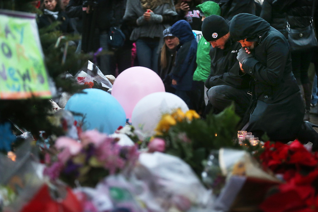 . NEWTOWN, CT - DECEMBER 16:  People gather at a memorial for victims near the school on the first Sunday following the mass shooting at Sandy Hook Elementary School on December 16, 2012 in Newtown, Connecticut. U.S. President Barack Obama visited the grief stricken town today.  (Photo by Mario Tama/Getty Images)