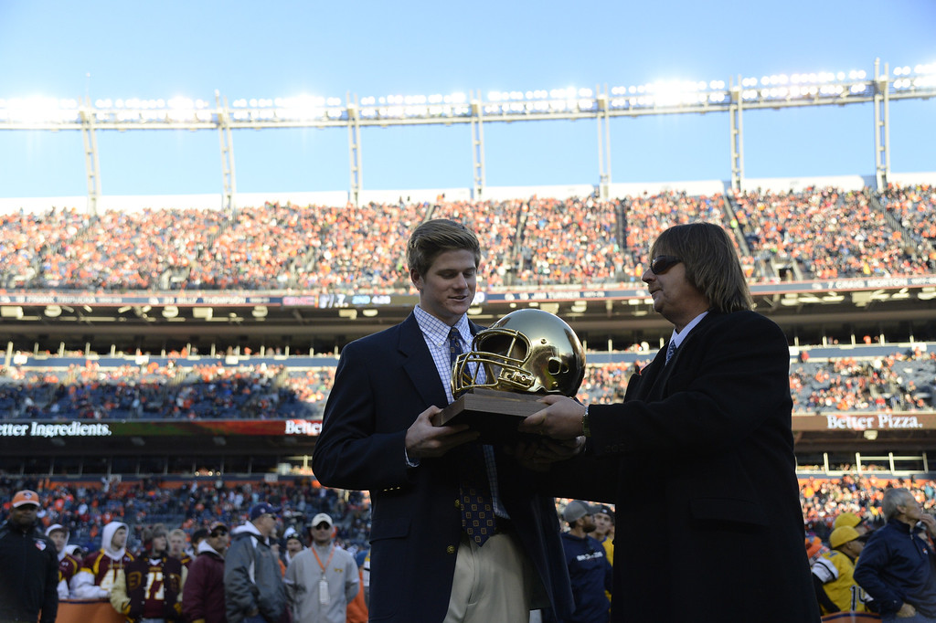 . DENVER, CO - DECEMBER 28: Mike Morean of Cherry Creek is The Denver Post\'s 64th Gold Helmet Award winner as the state\'s top senior football player, scholar and citizen. He was presented with the award by Denver Post reporter Neil Devlin during halftime of the Broncos game. The Denver Broncos played the Oakland Raiders at Sports Authority Field at Mile High on December 28, 2014. (Photo by AAron Ontiveroz/The Denver Post)