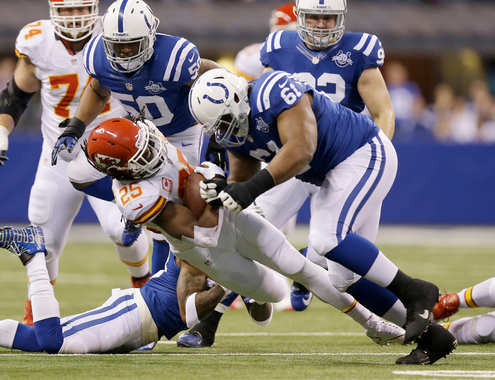 . Kansas City Chiefs running back Jamaal Charles (25) is tackled by Indianapolis Colts defensive tackle Jeris Pendleton (61) during the first half of an NFL wild-card playoff football game Saturday, Jan. 4, 2014, in Indianapolis. (AP Photo/Michael Conroy)