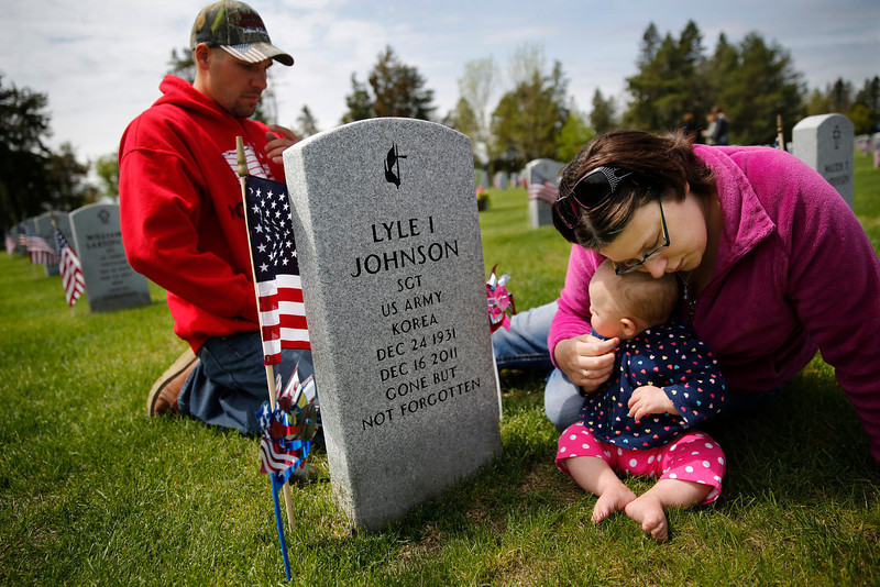 . Ryan Neal, wife Desiree and daughter Sophia pay a visit to deceased Korean War Purple Heart decorated Army Sgt. Lyle Johnson, who passed away in 2011, during the Memorial Day Service at the State Veterans Cemetery in Little Falls, Minn., Sunday, May 26, 2013. Desiree described her grandfather as a man who loved kids and spent a year and a half in a Denver hospital recovering from machine gun wounds.  (AP Photo/The Star Tribune, Richard Tsong-Taatarii)