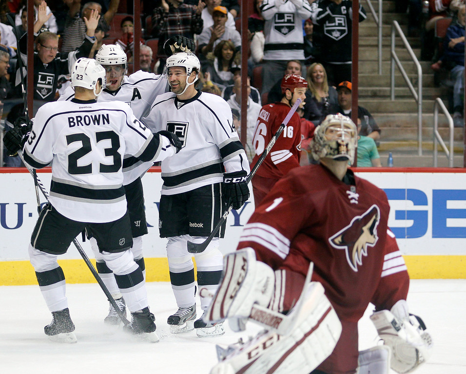 . Los Angeles Kings right winger Justin Williams (14) is congratulated by teammates Dustin Brown (23) and Anze Kopitar (11) after Williams scored a goal against Phoenix Coyotes goalie Jason LaBarbera (1) in the first period of an NHL hockey game Tuesday, April 2, 2013, in Glendale, Ariz. (AP Photo/Paul Connors)