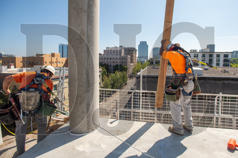 Mike Thompson, left, and Sputyá Mike Berry, both of Local 1503 and Lease Crutcher Lewis, remove slab edge formwork at the Canvas project site. (Josh Kulla/DJC)
