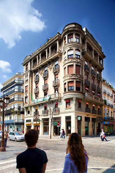 Pedestrians walking in front of Rafael Lora Building, work in Regionalist style by the architect Juan Talavera y Heredia (1936), Seville, Spain