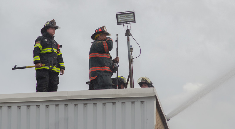 Fitchburg FFs Tim OKane (left) and Capt Gregg Normandin operate on the roof of New England Wooden Ware in Gardner during a 6th Alm on Sherman St.