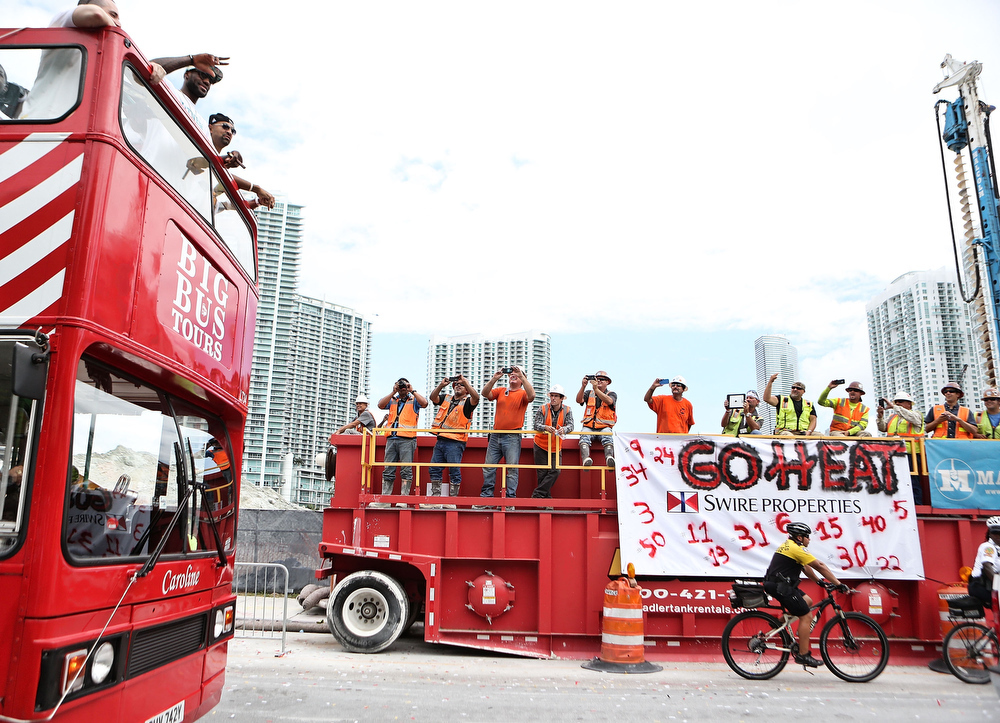 . People photograph forward Lebron James #6 of the Miami Heat  (L) as he rides a bus during the NBA championship victory parade on June 24, 2013 in Miami, Florida. The Miami Heat defeated the San Antonio Spurs in the NBA Finals. (Photo by Marc Serota/Getty Images)