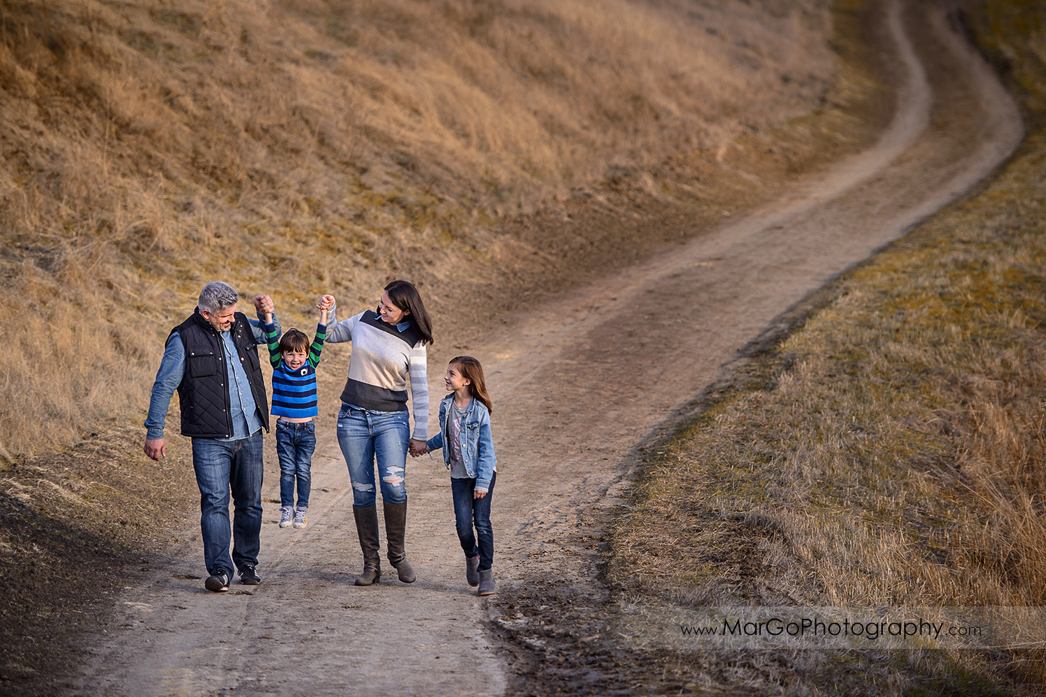 family of four wearing blue and grey clothes having fun walking down the hill during photo session at Diablo Foothills Regional Park in Walnut Creek