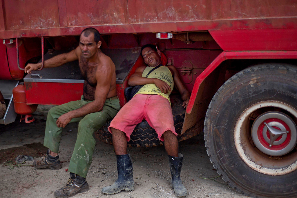 . In this Sept. 30, 2013 photo, men rest on their truck loaded with fruits and vegetables as they wait for the 114th Street Market to open on the outskirts of Havana, Cuba. Exhausted from being on the road all night, drivers grab a few winks wherever they can _ atop their cabs, on rickety cots, even in wheel wells. (AP Photo/Ramon Espinosa)