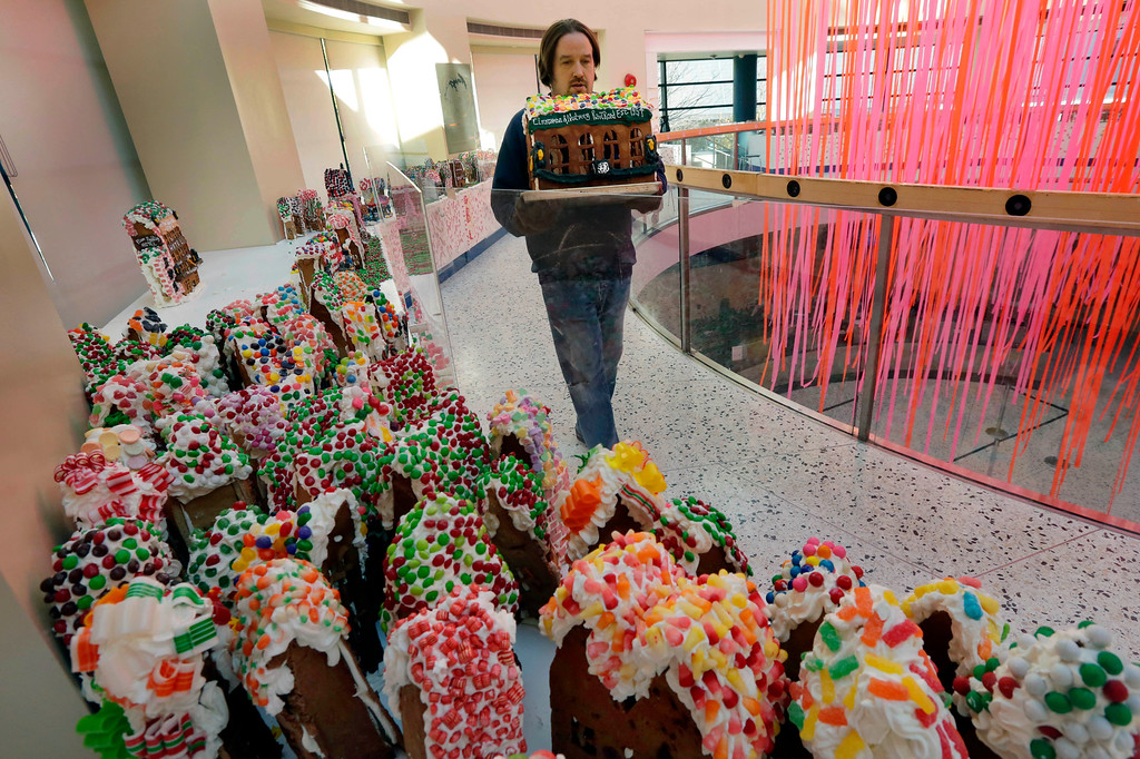 . Chef Jon Lovitch carries the Cinnamon & Nutmeg Railroad station, one of his gingerbread house creations, for placement in his GingerBread Lane display, at the New York Hall of Science, in the Queens borough of New York, Thursday, Nov. 13, 2014. Lovitch, a Manhattan chef who holds the Guinness record for creating the world\'s largest collection of gingerbread houses, is now going for another record, competing against himself by assembling more than 1,000 new ones. (AP Photo/Richard Drew)