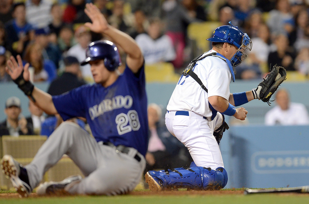 . Los Angeles Dodgers catcher A.J. Ellis catches the ball as Rockies baserunner Nolan Arenado scores in the 4th inning April 29, 2013 in Los Angeles, CA.(Andy Holzman/Staff Photographer)
