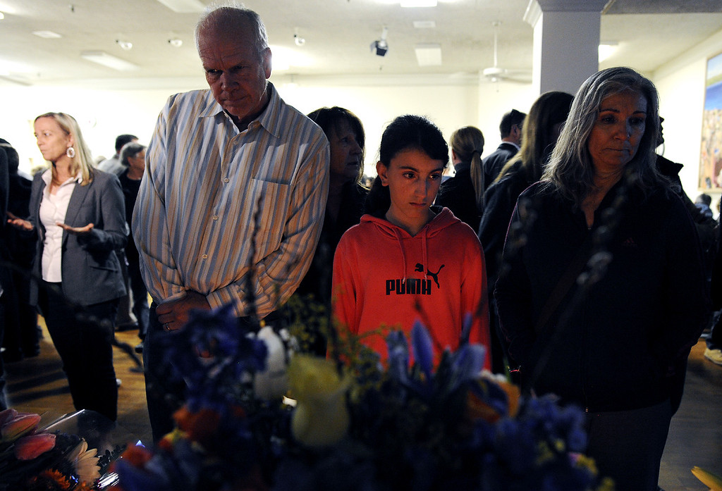 . Santa Cruz residents come to mourn the loss of two Santa Cruz police officers stop to observe a candlelight vigil set up at the Louden Nelson Community Center Wednesday evening (Matthew Hintz/Sentinel).