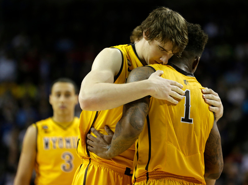 . Wyoming\'s Charles Hankerson Jr. (1) is hugged by teammate Jonathan Barnes, center, after Northern Iowa beat Wyoming 71-54 in an NCAA tournament college basketball game in the Round of 64 in Seattle, Friday, March 20, 2015. (AP Photo/Ted S. Warren)