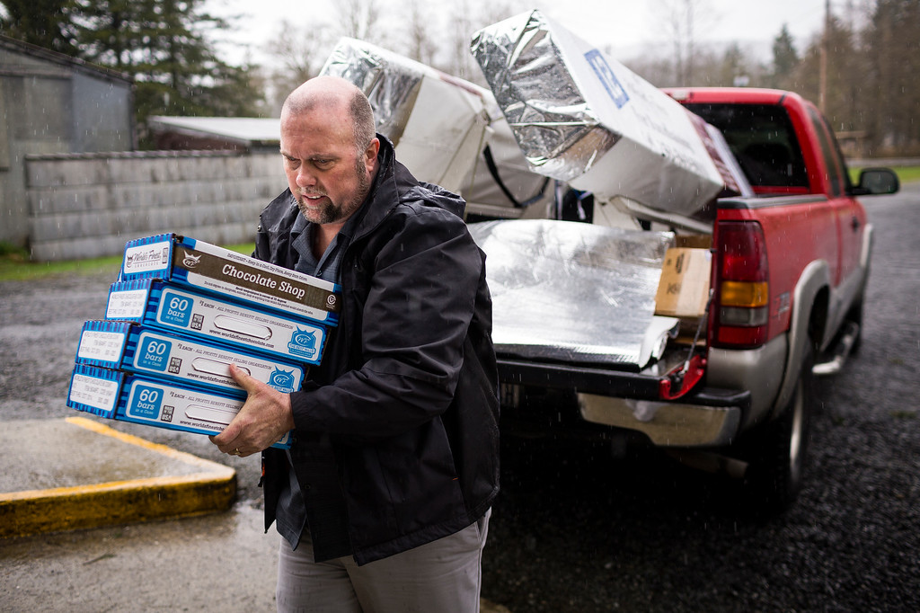 ". Gary Ray, pastor of the Oso Community Chapel, helps to load in a truck-full of chocolate bars as a donation for victims to serve as ""comfort food\"" Thursday, March 27, 2014, near Oso within Snohomish County, Wash. (AP Photo/seattlepi.com, Jordan Stead)"