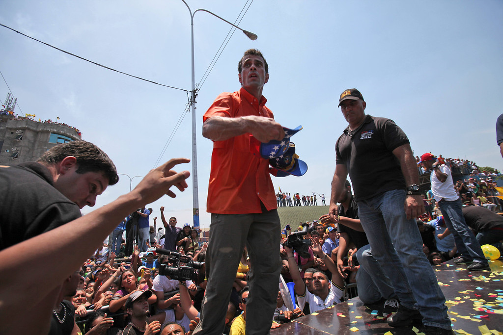 . Opposition presidential candidate Henrique Capriles throws out baseball caps to supporters at a campaign rally in San Fernando de Apure, Venezuela, Thursday, April 11, 2013. Capriles is running against the ruling party candidate Nicolas Maduro in the upcoming April 14 presidential election. (AP Photo/Fernando Llano)