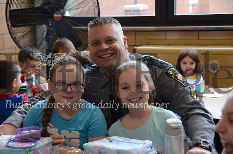 Trooper Michael Lewis visits with 4th grade students Alexa Coyle and Hannah Lewis at Butler Catholic School. Butler Catholic School had over a dozen state troopers for lunch Jan. 29 during Catholic Schools Week. submitted photo