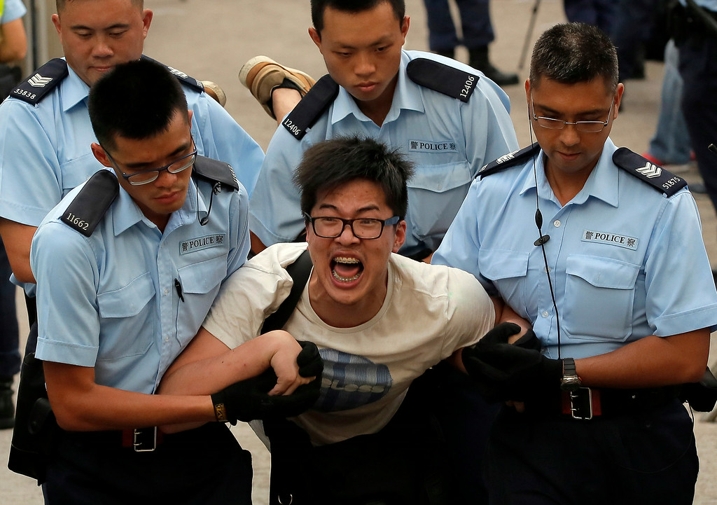 . A protester, center, is taken away by police officers after hundreds of protesters staged a peaceful sit-ins overnight on a street in the financial district in Hong Kong Wednesday, July 2, 2014, following a huge rally to show their support for democratic reform and oppose Beijing\'s desire to have the final say on candidates for the chief executive\'s job. (AP Photo/Vincent Yu)