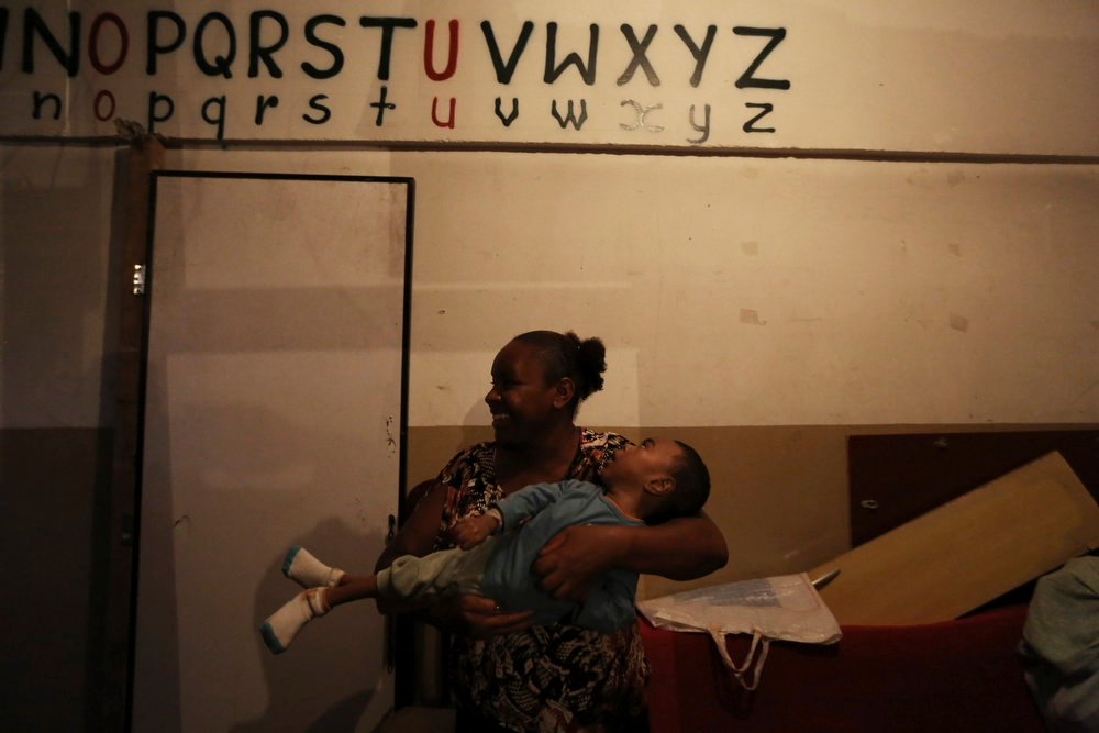 . Debora, 41, a member of Brazil\'s Movimento dos Sem-Teto (Roofless Movement), holds her disabled son Joao Vitor, 5, at an area that used to be a nursery and school in Sao Paulo March 10, 2013. More than 1,200 people from Brazil\'s roofless movement live in an explosion prone area that has been contaminated with methane since October 2012, local media reported. According to the Environmental Sanitation Technology Company in the State of Sao Paulo (CETESB) the soil and water from the groundwater are contaminated with methane. Picture taken March 10, 2013. REUTERS/Nacho Doce