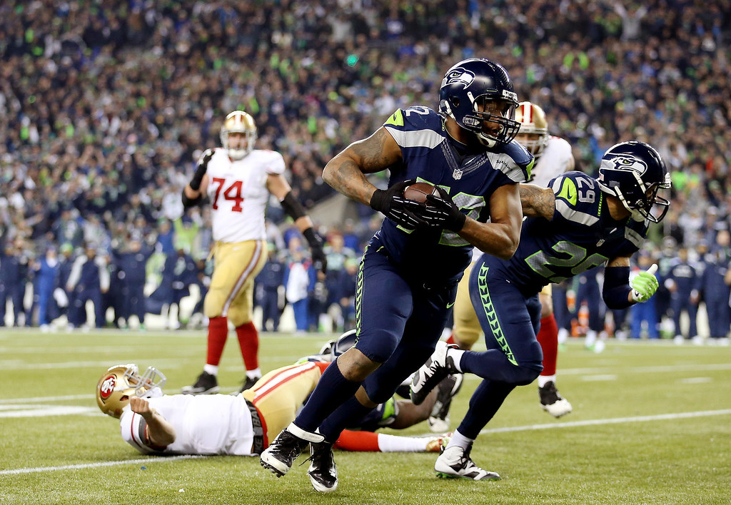 . Defensive end Michael Bennett #72 of the Seattle Seahawks recovers a fumble by quarterback Colin Kaepernick #7 of the San Francisco 49ers and runs for 17-yards in the fourth quarter during the 2014 NFC Championship at CenturyLink Field on January 19, 2014 in Seattle, Washington.  (Photo by Christian Petersen/Getty Images)