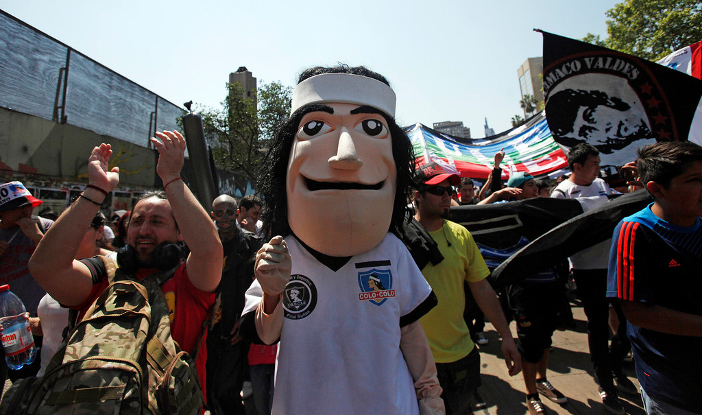 . A protester wearing a puppet mask of the late Mapuche Indian Colo Colo, the symbol for a local soccer team named after him, attends a march against the commemoration of the discovery of America by Christopher Columbus in Santiago, Chile, Saturday, Oct. 12, 2013. The march was organized by members of indigenous groups demanding autonomy and the recovery of ancestral land. Protesters also demonstrated against Chile\'s anti-terrorism law, under which many Mapuche Indians are under arrest. Saturday is the the anniversary of Columbus\' 1492 arrival in the Americas. (AP Photo/Luis Hidalgo)