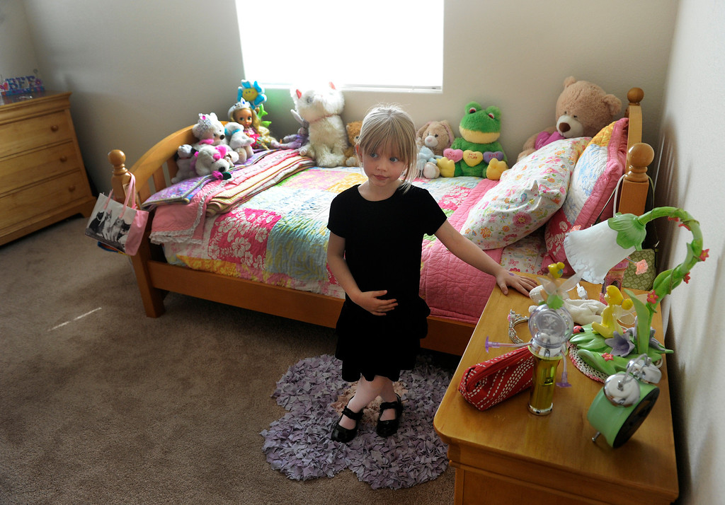 ". Alissa McCutchan, 6, shows off her room in her new home in the Parkside subdivision. She and her father, and younger brother Cameron lost everything in the fire except for a few items her dad could throw in the back seat. Her grandmother, ""nana\"" Genevieve Gustavson helped her get the new items to decorate her room.  (Photo By Kathryn Scott Osler/The Denver Post)"